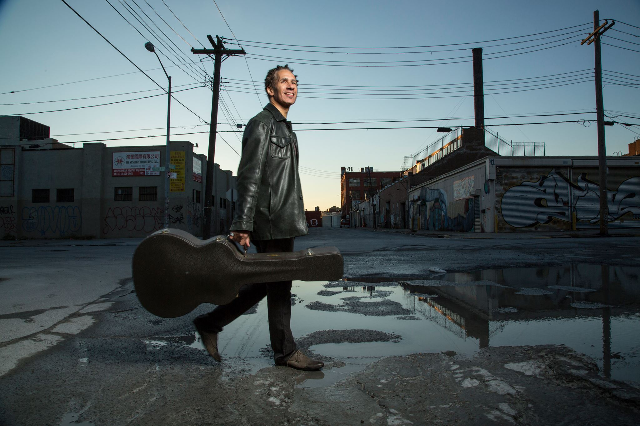 guitarist David Gilmore walking down a rain-soaked street
