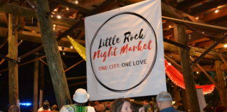 """a banner that says """"Little Rock Night Market,"""" suspended above a crowd at Bernice Garden in Little Rock"""