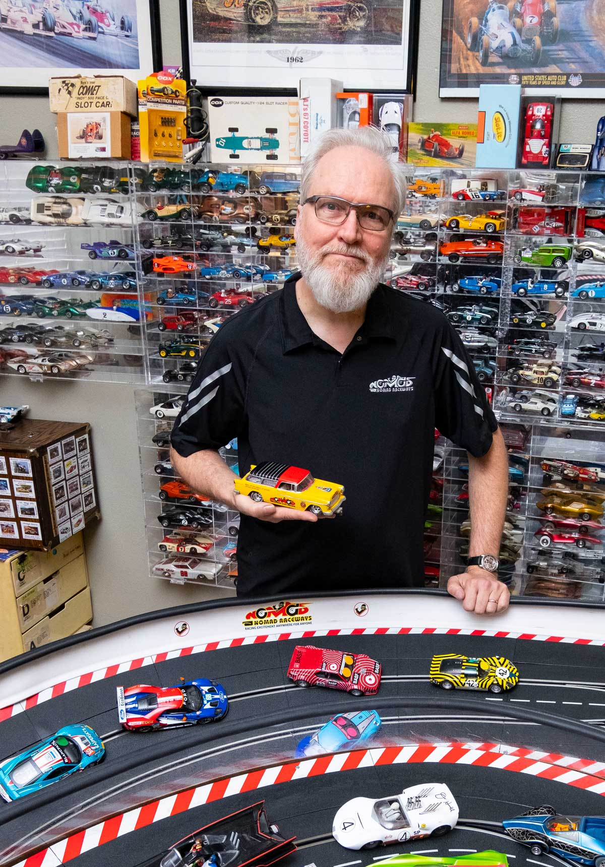 Picture of Jim Cunningham holding slot cars next to his slot car track