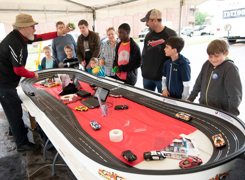 picture of Jim Cunningham and spectators around Cunningham's slot car race track
