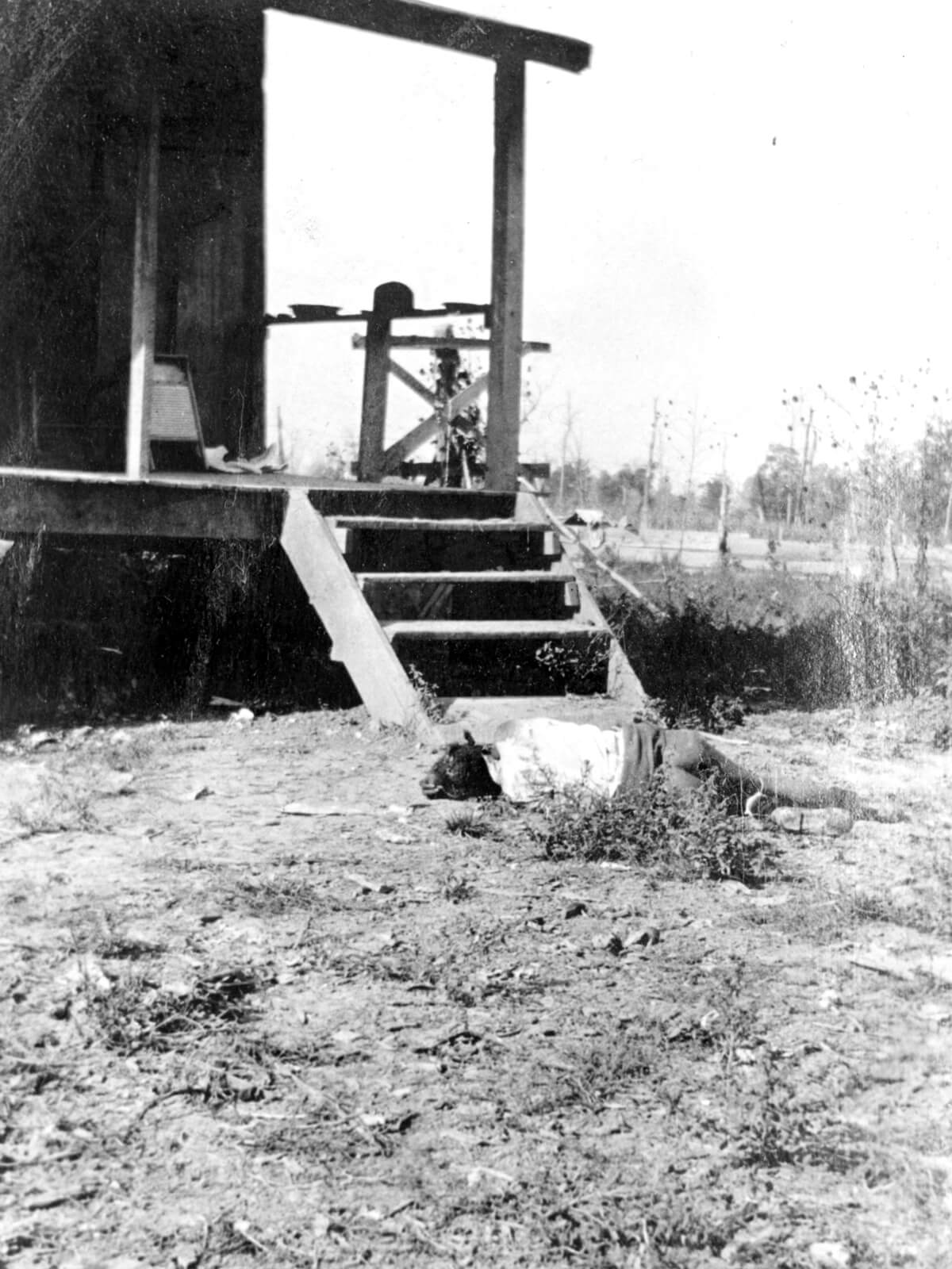 Photo of person face-down, dead, in front of a house.